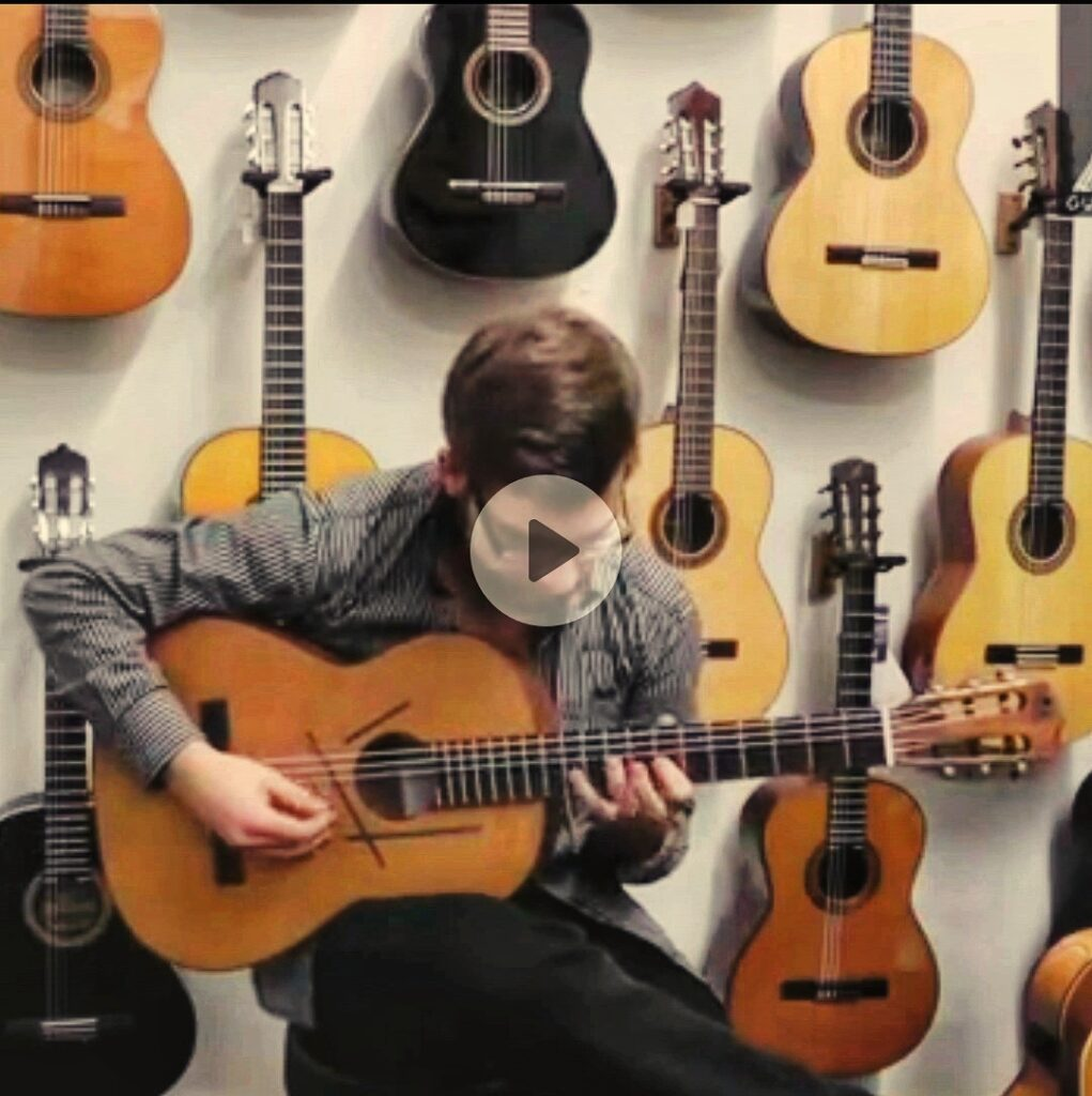man plays flamenco guitar in front of a wall with many guitars